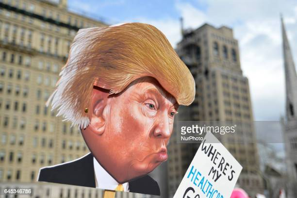 At a Feb 25 2017 Affordable Care Act repeal protest rally in Philadelphia PA artist Carla Krash holds up a sign with a cartoon image of Donald Trump...