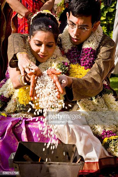 At a Hindu wedding ceremony bride Shweta Singhal and groom Rohit clasp each others hands with a handful of puffed rice which is then thrown into a...