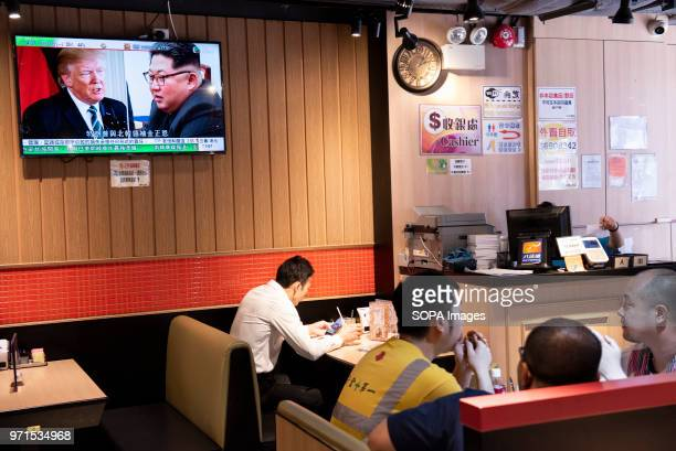 At a local restaurant in Hong Kong people watch a TV screen showing images of US President Donald Trump and North Korea leader Kim Jongun during a...