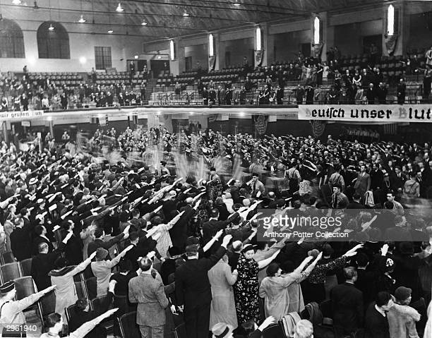 At a Nazi rally in the White Plains Hall the audience gives a Nazi salute as flags are paraded down the hall's center aisle White Plains New York...