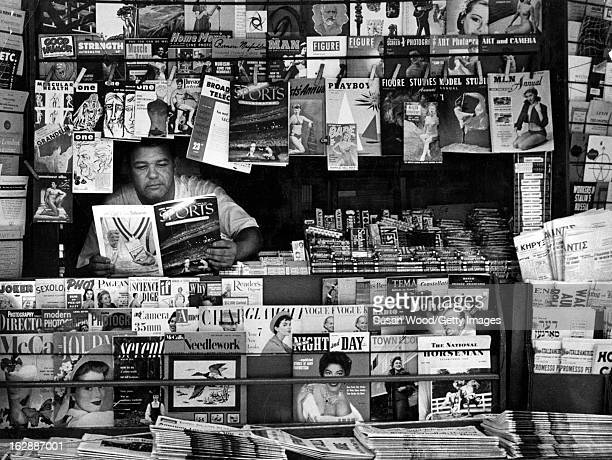 At a newstand, a vendor reads an issue of Sports Illustrated magazine as he waits for cistomers, New York, New York, August 1954.
