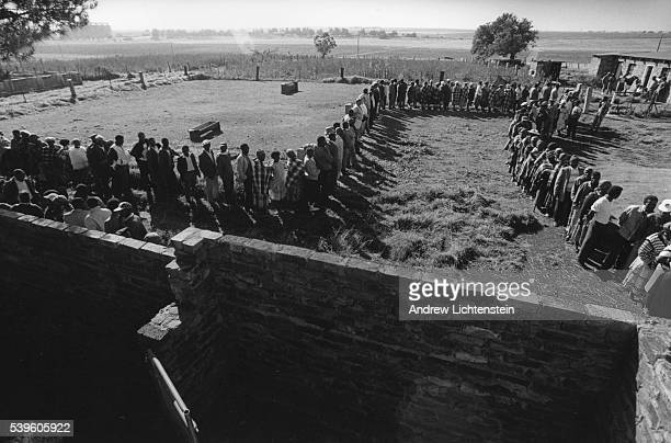 At a polling station in the Orange Free State rural African farm workers stand in line to vote in South Africa's first democratic election officially...