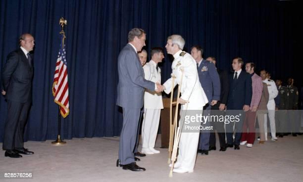 At a predinner reception US President Richard Nixon shakes hands greets former North Vietnamese prisoner of war Captain John McCain Washington DC May...