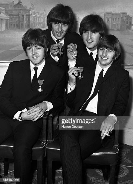 At a press reception held in the Saville Theatre The Beatles Paul McCartney George Harrison John Lennon and Ringo Starr hold up the MBEs which they...