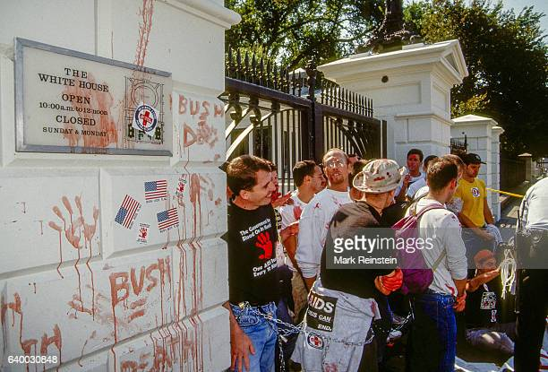 At a rally in front of the White House ACT UP demonstrators many smeared in fake blood chain themselves to the Northwest Gate Washington DC September...