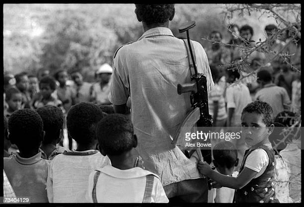 At a school for orphans and children of EPLF fighters a little girl clings to her armed father's shirt during a surprise visit 27th June 1978