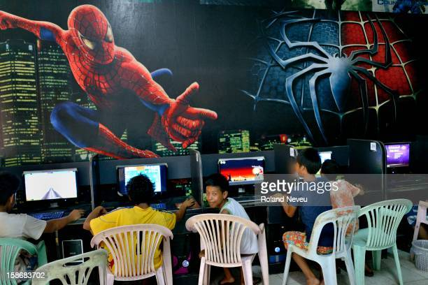 At a shopping center in Mawlamyine a group of children enjoy the afternoon at a cybercafe adorned with giant spiderman picture