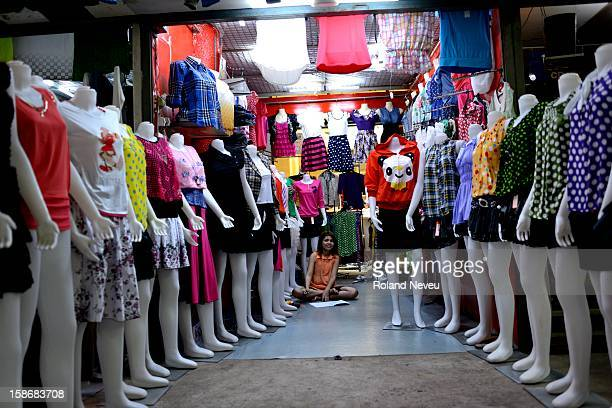 At a shopping center in Mawlamyine a woman is sitting in her fashion shop linedup with dressed mannequins