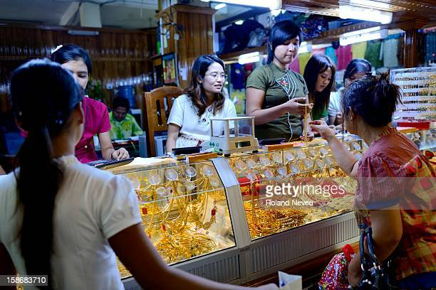 At a shopping center in Mawlamyine women looking at and choosing gold ornaments while chatting with the several shopkeepers of the gold shop