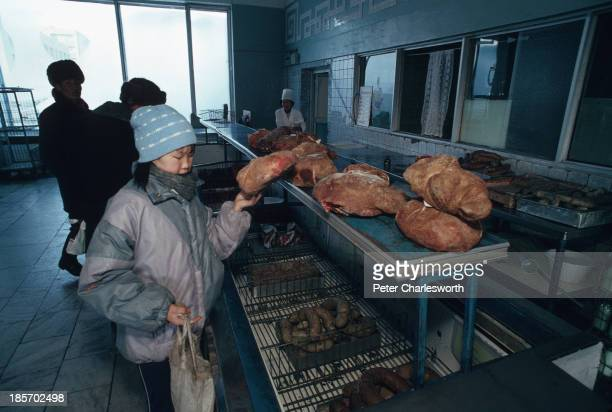 At a state-run butcher's shop a woman selects a piece of meat. Choice is exceedingly limited, in fact more often than not, shoppers have to queue in...