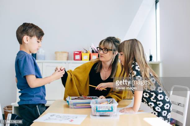 at a table, a teacher sits with two students while they color - calabasas stock pictures, royalty-free photos & images