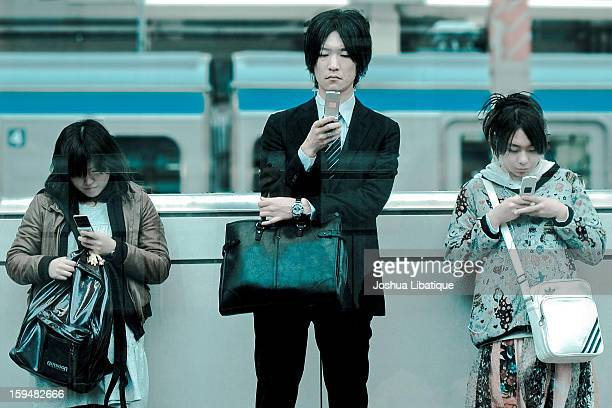 CONTENT] At a train station in Tokyo Japan three young Japanese adults check their cell phones while waiting for the train Original description on...