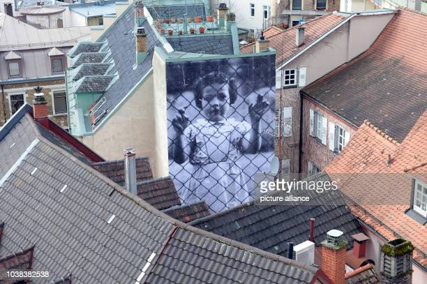 At a wall hangs a photo installation of the French artist JR in BadenBaden Germany 27 February 2014 The exhibition takes place from 01 March 2014 to...
