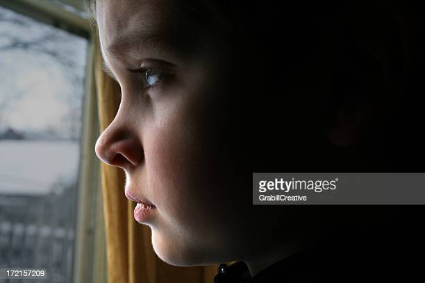 At a Window: Boy Stares Sadly Outside