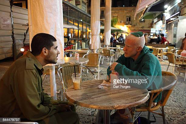 At an unidentified cafe in the Ben Yehuda Pedestrian Street a pair of young men talk as they sit together at an outdoor table Jerusalem Israel...