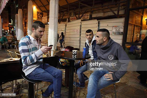 At an unidentified cafe in the Ben Yehuda Pedestrian Street a trio of young men one with a smartphone sit together at an outdoor table Jerusalem...