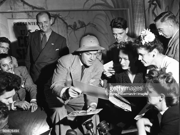 At an unspecified USO Campsponsored event Britishborn American comedian and actor Bob Hope a pith helmet on his head as he looks at photographs with...
