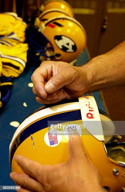 At Anaheim High School field equipment manager Ron Ledesma applies stickers to varsity football helmets The stickers are a tribute to former student...