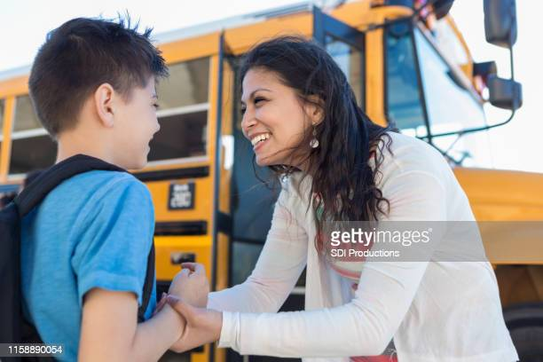 at bus stop, mid adult mom encourages son before school - aunt stock pictures, royalty-free photos & images