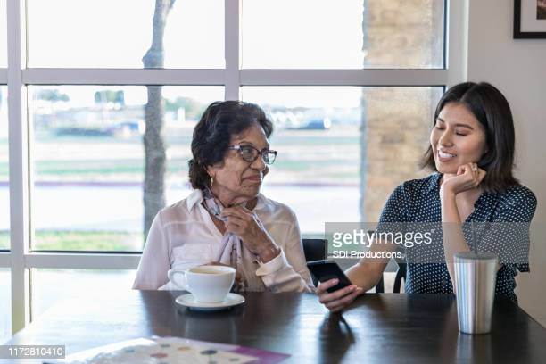 at cafe, mother watches daughter enjoy video on smart phone - minority groups stock pictures, royalty-free photos & images