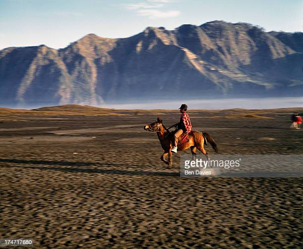 At dawn a villager on horseback gallops across the sands at Mount Bromo the spectacular volcanic peak that is situated high up in the Tengger...