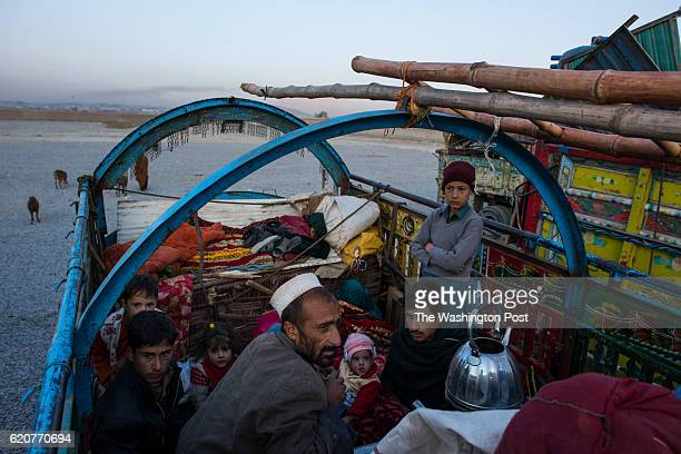 At dawn after driving from Pakistan the previous day a family of Afghans wake up and boil tea after a night sleeping on top of the trucks that...