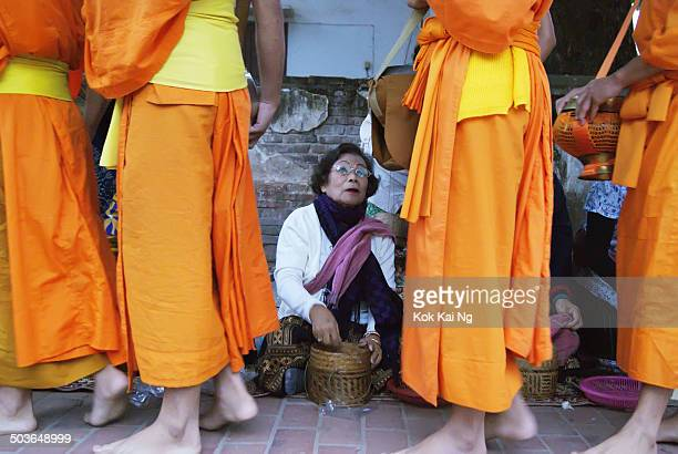 CONTENT] At dawn every morning in Luang Prabang monks walk around the town in a line to collect alms from devotees Some like this lady travel from...
