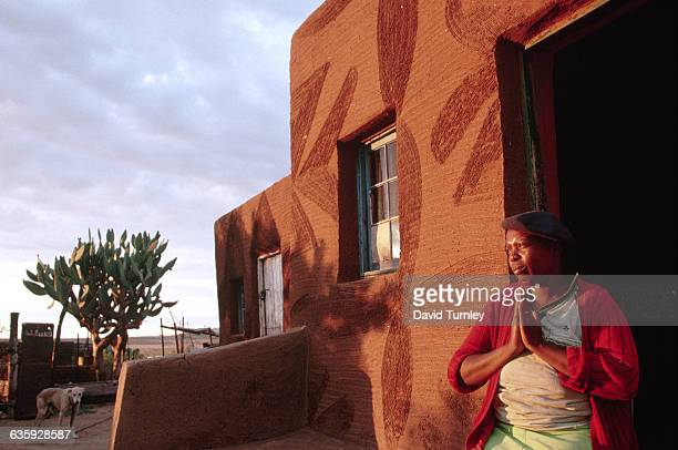 At daybreak a South African farm laborer prays at the door to her home made from mud and daub construction outside Bloemfontein | Location Near...