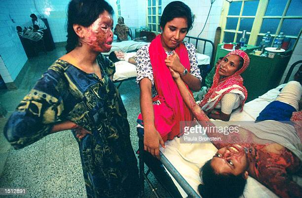 At Dhaka's only hospital burn unit at Dhaka medical college Reba a 19 year old Bangladeshi woman lying on bed at right is tended to by two relatives...