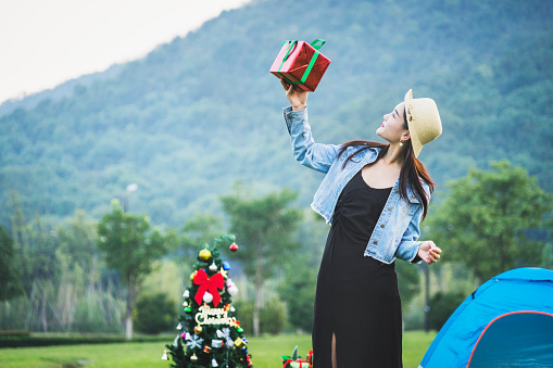 At dusk of an outdoor Christmas party, a young Asian woman runs freely on the lawn beside the party and throws out a gift box. She is happy and happy. 1058438232