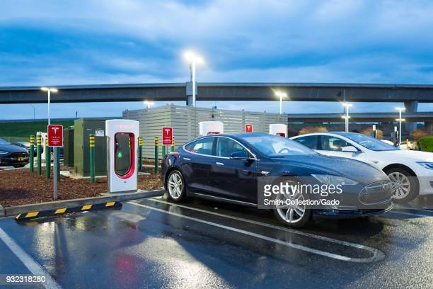At dusk Tesla Motors electric cars are plugged in and charging at a Tesla Supercharger electric vehicle charger in Pleasanton California March 12 2018
