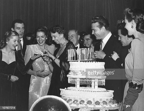 At her husband's birthday celebration in the Statler Hotel American First Lady Eleanor Roosevelt gives actress Joan Fontaine a piece of birthday cake...
