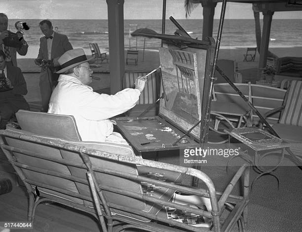 At his ease, and with the usual cigar in his mouth, former British Prime Minister Winston Churchill places a few deft daubs on his canvas as he...
