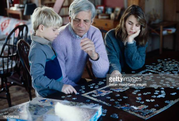 At his summer home, American writer and journalist George Plimpton and his children, Taylor Ames Plimpton and Medora Ames Plimpton, work on a jigsaw...