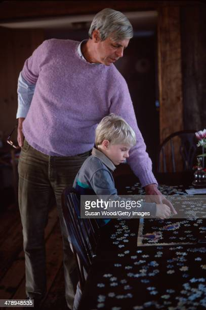 At his summer home, American writer and journalist George Plimpton and his son, Taylor Ames Plimpton, work together on a jigsaw puzzle, Wainscott,...