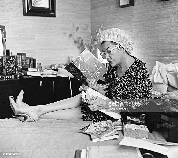 At home as she dries her hair American actress Gloria Swanson reads a book about cell biology New York New York 1960