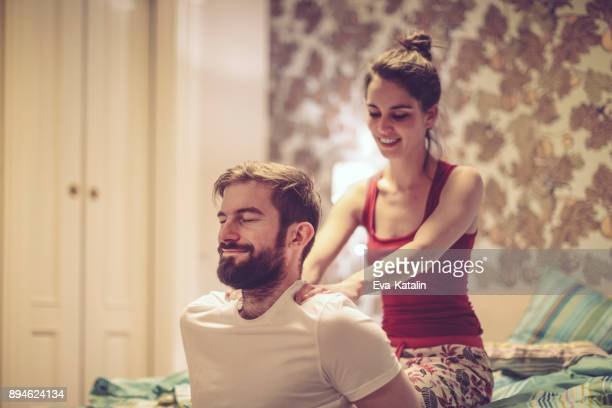 at home - husband massage wife stock photos and pictures