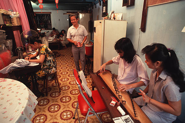 At home with the Luong family Luong Trang teaches a girl how to play music on a traditional Vietnamese Instruments called a Dan Tranh She gives music...