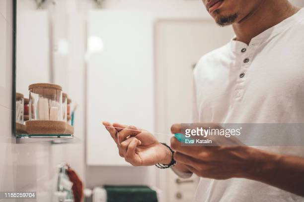 at home - young man brushing his teeth - dental floss stock pictures, royalty-free photos & images