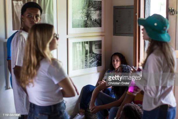 At Instituto Terra the colaborator Jaqueline guides students from a school on a visit through the room where photos taken by Sebastião Salgado are...