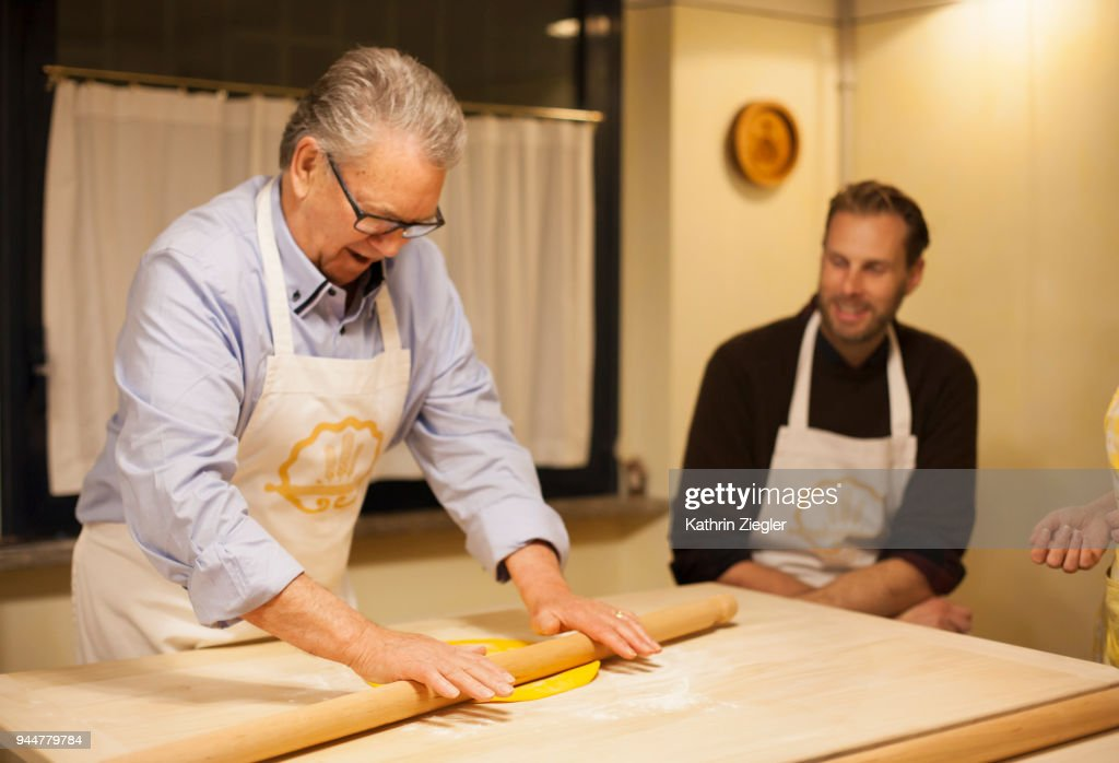At Italian cooking school: Senior man rolling out dough using rolling pin : Stock Photo