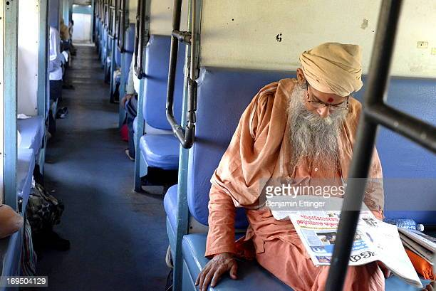 At Jhansi Junction railway station in north central India, an early arrival on the train to Allahabad reads the newspaper while waiting for the train...
