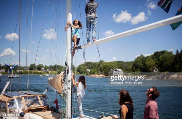 At left Tucker and Victoria Bradford watch as their daughter Ruby center climbs up the mast of their sailboat with her friends Noah Borel and Lilo...