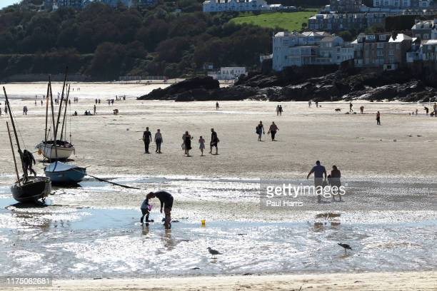 At low tide holiday makers walk across the harbor beach sand towards the Ocean at St Ives during the 2019 September Summer Festival St Ives has...