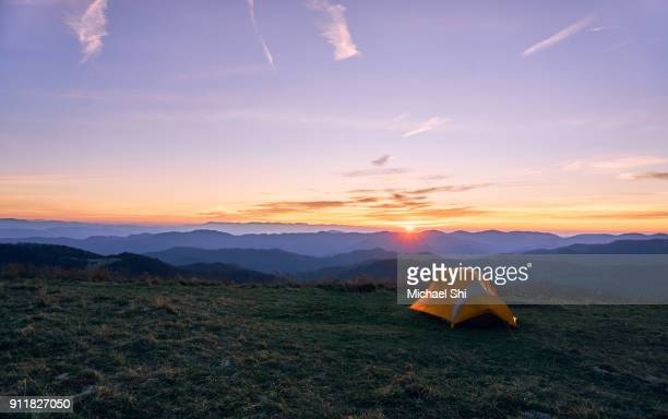 at max patch, north carolina, a small yellow tent on a meadow on the appalachian trail is greeting sunrise underneath the blue sky with blue ridge mountains in the distance. - appalachian trail stock pictures, royalty-free photos & images