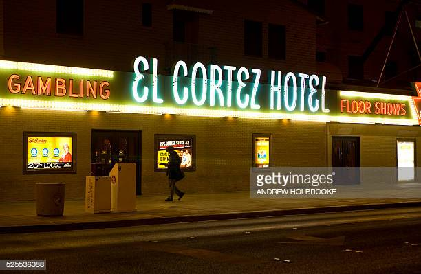 At night downtown on Freemont Street a man passes The El Cortez Hotel and casino where Bugsy Siegel was a partner