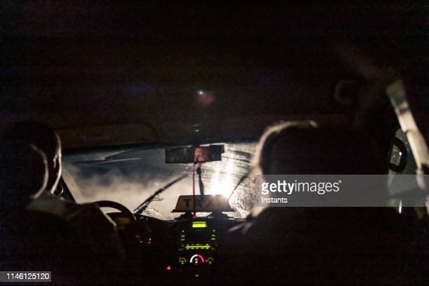 at night, in havana, a cab driver at work with a male passenger sitting next to him in the front seat. - taxi driver stock pictures, royalty-free photos & images