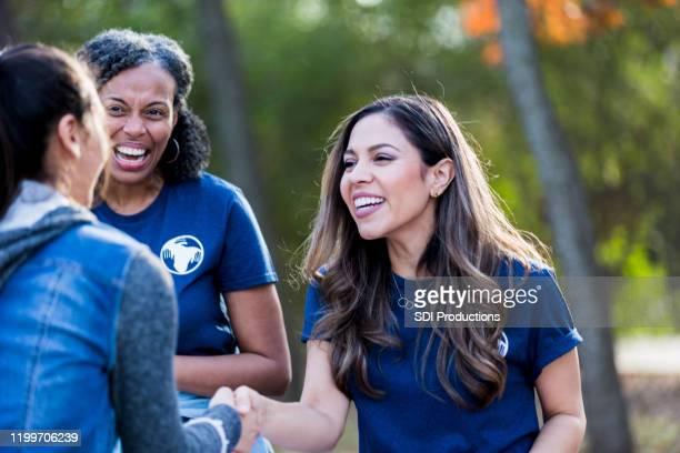 bij park cleanup event, twee vrouwen begroeten en schudden handen - liefdadigheidswerk stockfoto's en -beelden