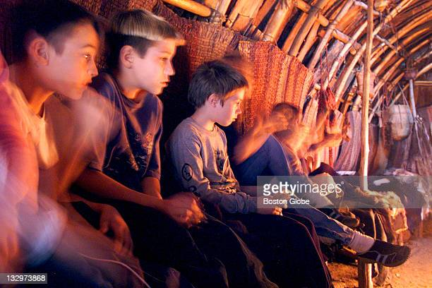 At Plimoth Plantation children sit inside an Indian hut lit by a fire as they listen to a fur trading account by the Wampanoags