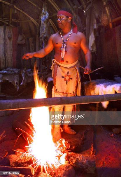At Plimoth Plantation Wampanoag Darel Wixon stands over a fire he made inside a hut made from tree bark He is from Mashpee